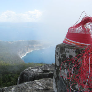 Wire basket on a lichen-covered rock, in the clouds on top of Mt Bishop and Clerk, Maria Island, Tasmania.