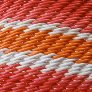 Detail of wire basket weave showing bands of red, pink, white and orange telephone wires.